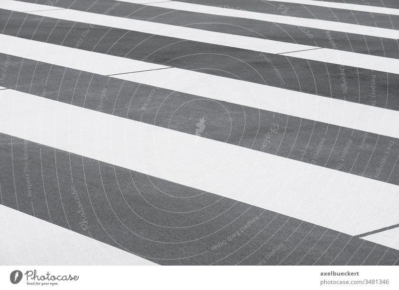 Nahaufnahme eines Zebrastreifens Asphalt Straße Markierung Hintergrund Streifen gestreift grau liniert abstrakt Muster leer niemand Verkehr Straßenbelag