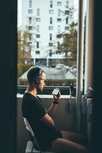 Mann mit Kopfhörern sitzt auf dem Balkon in der Abendsonne und sieht etwas auf seinem Smartphone an, Konzept Zuhause bleiben und Social Distancing Medien