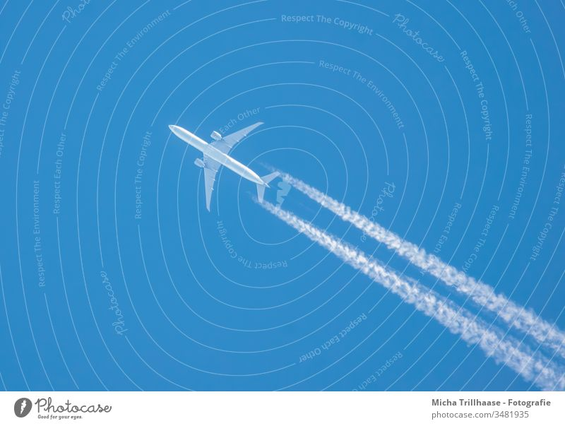 Flugzeug und Kondensstreifen am blauen Himmel Tragflächen Triebwerke Flugreise reisen Tourismus Touristen Fernreisen Umwelt Klima Urlaub Ferien Urlaubsreise