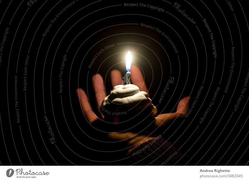 Trauriger Geburtstagskuchen. Konzept der Traurigkeit, sich allein zu fühlen. Hand hält einen Geburtstagskuchen für eine Person mit einer Kerze