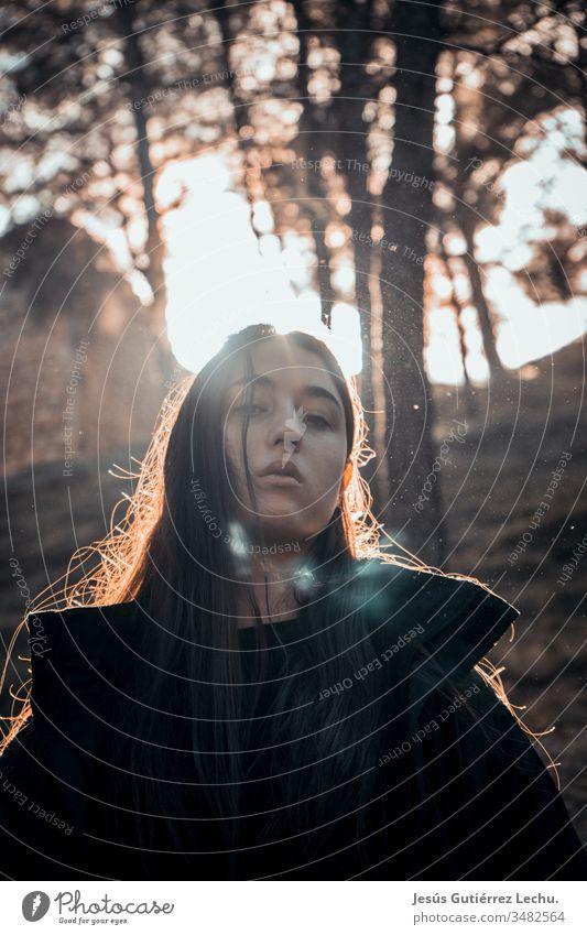junges Mädchen mit ernstem Blick mit starkem Kontrast im Hintergrund zur Sonne Kaukasier Dame klassisch Bekleidung Lifestyle Stil Mode attraktiv Frau