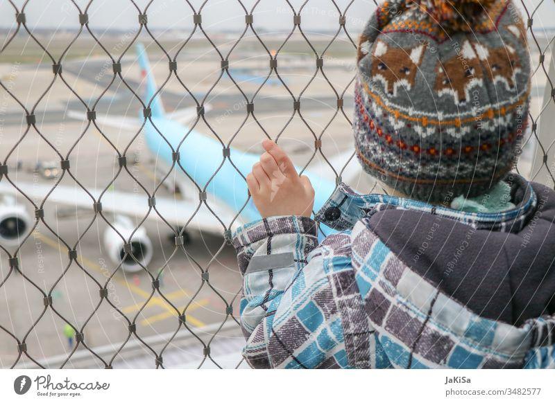 Kind am Zaun der Fluhafenabsprerrung mit Blick auf ein Flugzeug auf dem Flugfeld Mensch Ferien & Urlaub & Reisen Luftverkehr Himmel fliegen Außenaufnahme