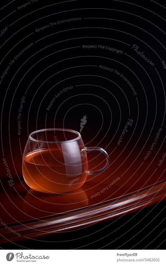 Tasse roter Tee auf einem luxuriösen Tisch mit schwarzem Hintergrund Getränk heiß Aufguss brauen Glas Holz hölzern Reflexion & Spiegelung dunkel Minze liquide