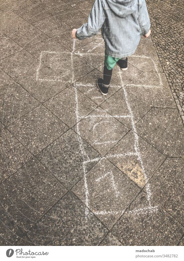 Hickelkasten spielen - Kind springt von Zahl zu Zahl auf mit Kreide gemalten Kästen - altes Kinderspiel Spiel hüpfen springen Spaß Außenaufnahme Spielen
