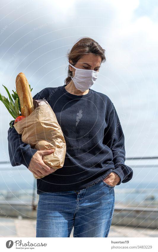 Frau mit Schutzmaske kommt mit dem Kauf nach Hause Coronavirus Mundschutz Pandemie Seuche Virus medizinisch Infektion Menschen behüten Großstadt covid-19