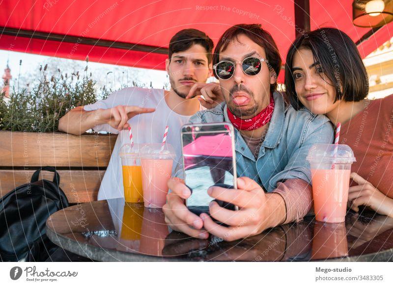 Drei junge Freunde beim Selfie mit Telefon. Glück Spaß Zusammensein Treffpunkt vier Freizeit Blick Person Sitzen Genuss Fröhlichkeit Smartphone Partnerschaft