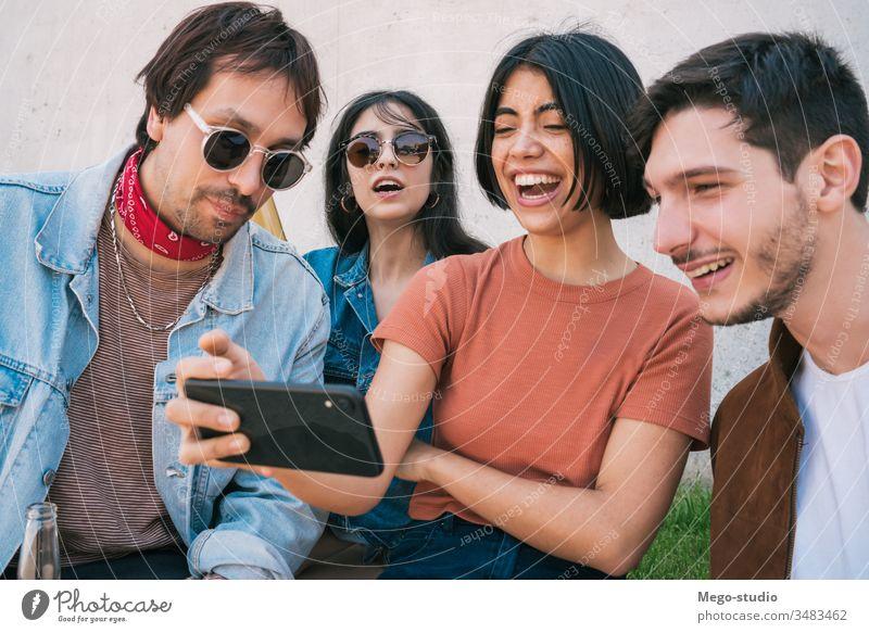 Gruppe von Freunden, die sich etwas auf einem Smartphone ansehen. Mobile Telefon Freundschaft Lifestyle Porträt Beteiligung urban modern Sitzung Freude Genuss