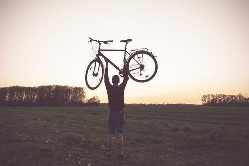 Mann hebt Fahrrad in die Luft Fahrradfahren Fahrradtour Liebe Natur Rad Naturerlebnis draußen gutes Wetter Feld hoch hochheben stark stärke Abenddämmerung