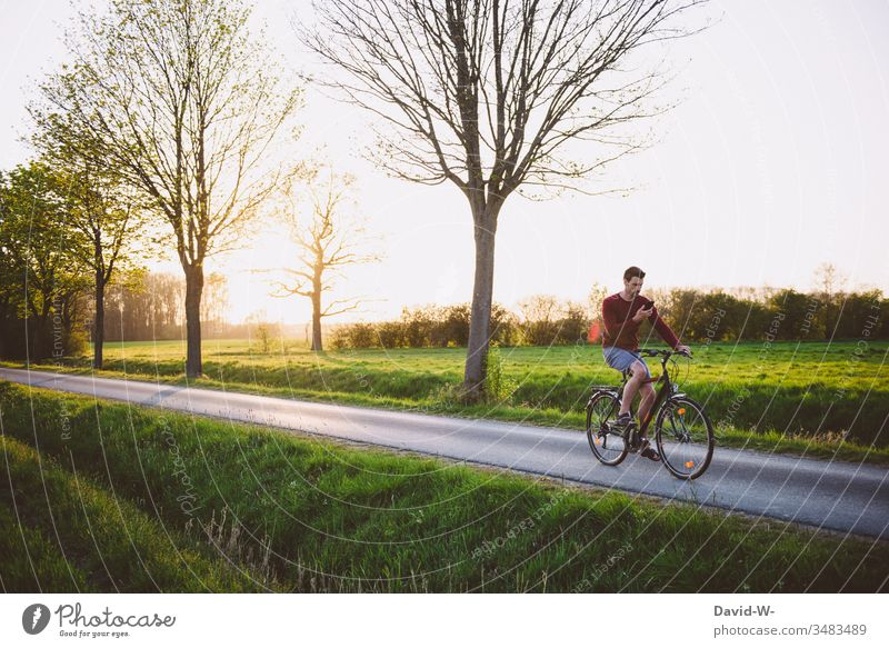 Mann fährt mit dem Handy in der Hand Fahrrad durch die Natur Fahrradfahren Fahrradtour Abgelenkt Sonnenstrahlen Rad Naturerlebnis draußen gutes Wetter Feld