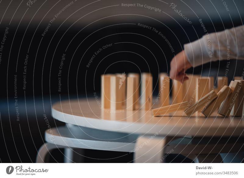 Kind spielt Domino mit Holzklötzen Kindheit Dominosteine Spielen Spaß haben Freude beschäftigung Hand umwerfen Finger Fröhlichkeit Freizeit & Hobby niedlich