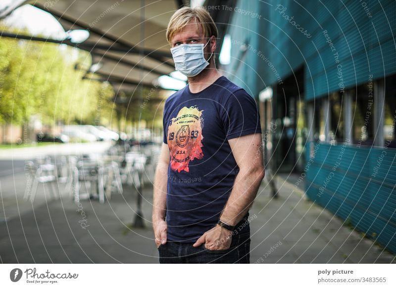 Porträt eines Mannes mit einer Schutzmaske der vor einem Gebäude steht, biologische Gefahr durch Coronavirus: Covid-19-Gefahr Person Epidemie Virus Grippe