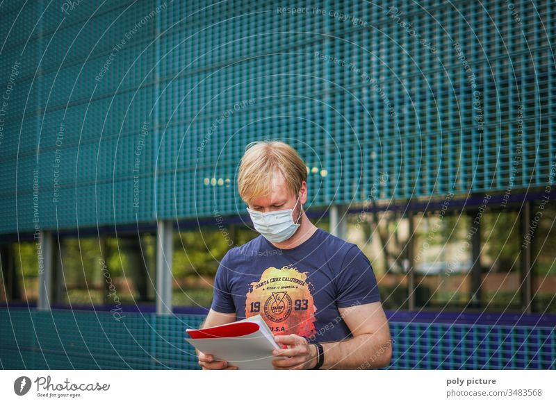 Porträt eines Mannes mit einer Schutzmaske der eine Bericht ließt, biologische Gefahr durch Coronavirus: Covid-19-Gefahr Person Epidemie Virus Grippe