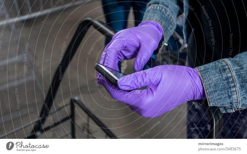 Warten auf der Einkaufslinie soziale Distanzierung und SMS auf dem Handy mit violetten Operationshandschuhen Texten am Mobiltelefon