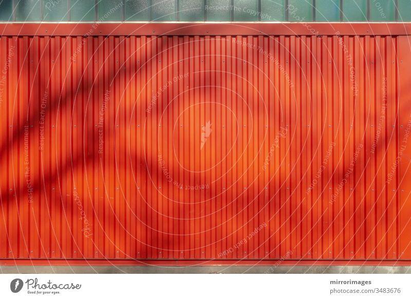 im Freien verwitterte vertikale rote Wand mit rotem Wandsiding im Hintergrund mit Baumschatten Seitengleis-Textur Metalltextur gerillt Leichtmetall industriell