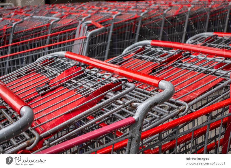 metallischer und roter Einkaufswagen Wagen in Reihe Einzelhandelskaufhaus Consumer Business-Konzept verschachtelt geparkt schieben Nahaufnahme Stapel Industrie