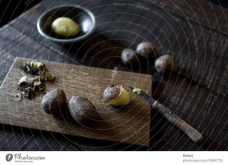 Pellkartoffeln auf Holzbrettchen mit Messer pellkartoffel schälen gesund geschält schale holzbrett kochen stilleben layflat messer alt pellen mittag anrichten