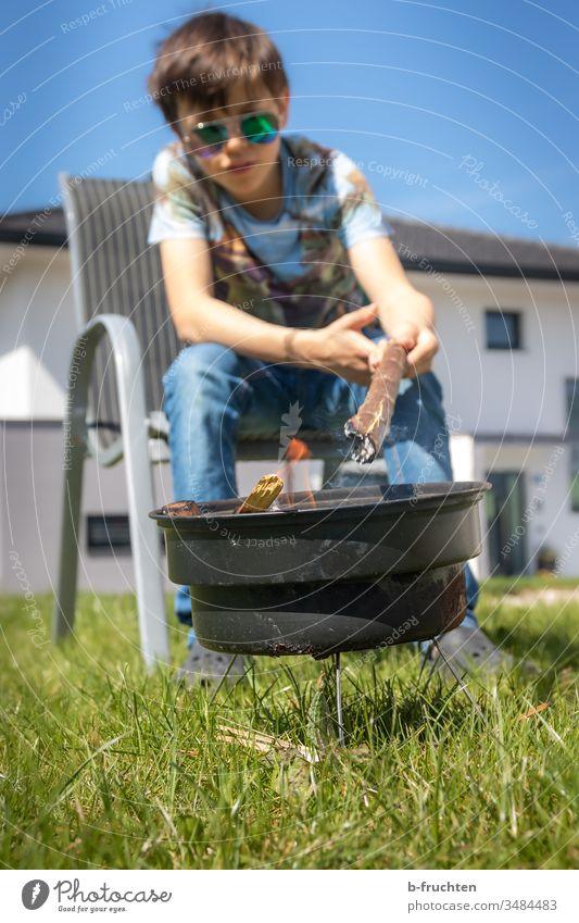 Schulkind sitzt im Garten bei einer kleinen Feuerstelle grillen Griller Grillsaison Grillplatz Grillen Außenaufnahme Kind Junge halten Ast brennen anzünden