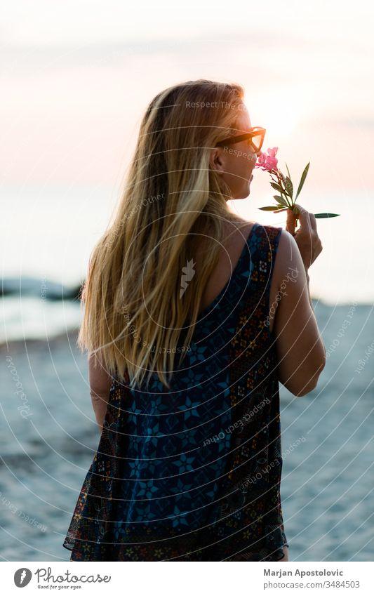 Junge Frau genießt Sonnenuntergang am Strand Erwachsener schön Schönheit sorgenfrei Abenddämmerung Genuss exotisch Blume Freiheit Spaß Mädchen Fröhlichkeit