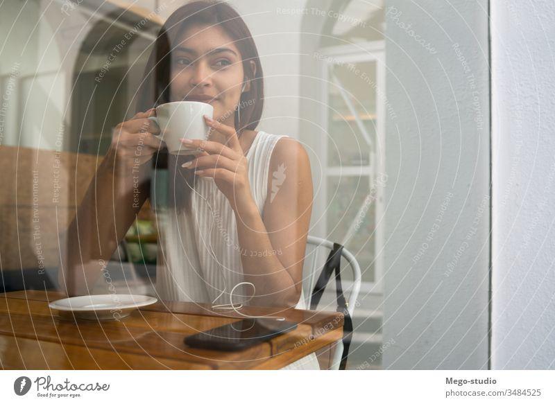 Junge Frau trinkt im Café eine Tasse Kaffee. jung Porträt Latein Kaffeehaus im Freien brünett Freizeit selbstbewusst Lifestyle Erfrischung Selbstvertrauen
