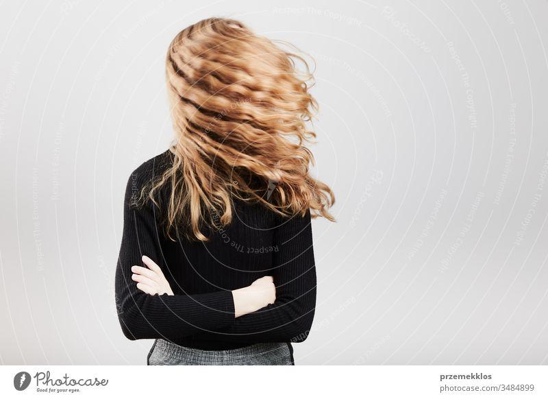 Porträt einer hübschen fröhlichen jungen Frau mit verschränkten Armen stehend über einem grauen, einfarbigen Hintergrund Mädchen Lifestyle positiv Teenager