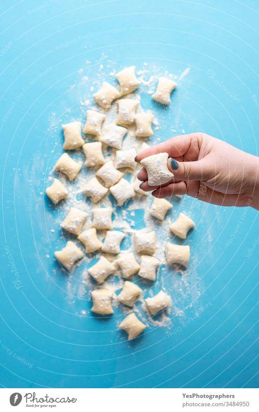 Käse-Gnocchi ungekocht in der Hand des Kochs. Haufen frischer Gnocchi-Knödel Italienisch obere Ansicht blau Essen zubereiten Küche Diät Abendessen Europäer