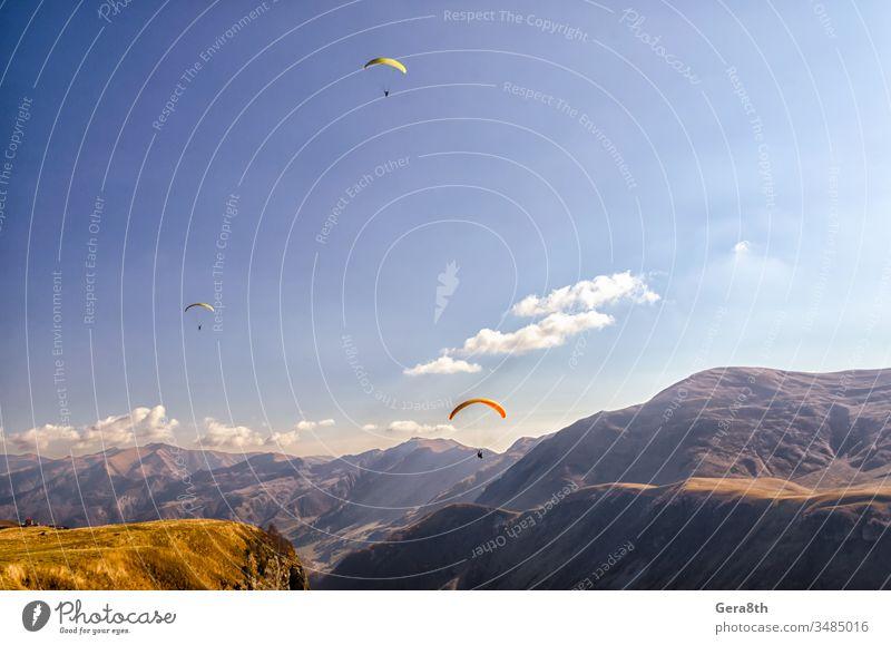 drei Gleitschirmflieger am Himmel vor dem Hintergrund der kaukasischen Berge Kaukasus Adrenalin Wolken Tag Europa extremal Extremsport Fliege fliegen Gras hoch