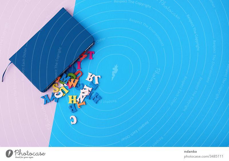 blaues Notizbuch und verstreute mehrfarbige Holzbuchstaben auf einem abstrakten Hintergrund farbenfroh oben blanko Business zugeklappt Farbe Konzept kreativ