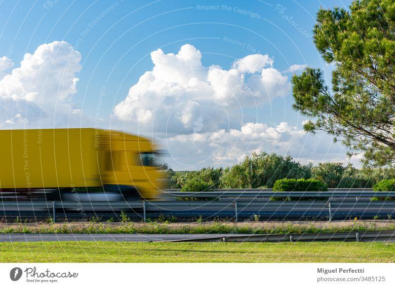 Gelber Lastwagen in Bewegung, der auf der Autobahn neben einem Baum und einem blauen Himmel mit Wolken fährt. Anhänger Ladung Straße Feld Landschaft Verkehr