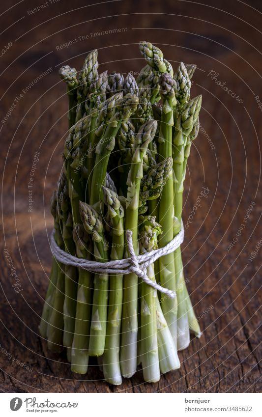 frischer grüner Spargel auf dunklem Holz Bündel Spargelbündel Planke Saison saisonal Gourmet String Küche Zutaten Antioxidans gesundes Essen Sprossen