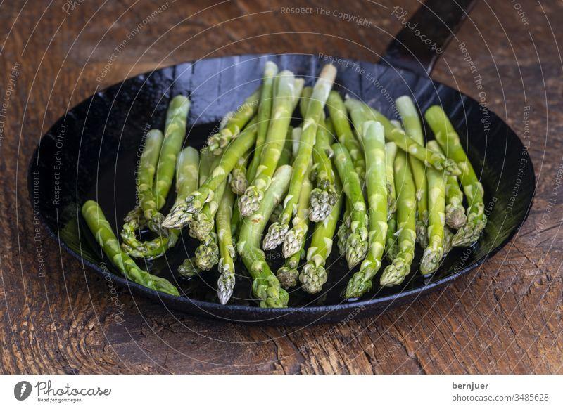 frischer grüner Spargel in einer Pfanne auf dunklem Holz Spargelpfanne Planke Saison saisonal Gourmet String Küche Zutaten Antioxidans gesundes Essen kochen