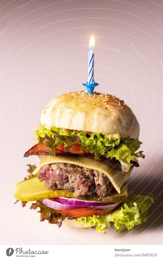 Nahaufnahme eines einzelnen Cheeseburgers Kerze Geburtstag Feier Party Partyfood knusprig fastfood geröstet Bio patty rucola gebacken sesam ketchup Gourmet