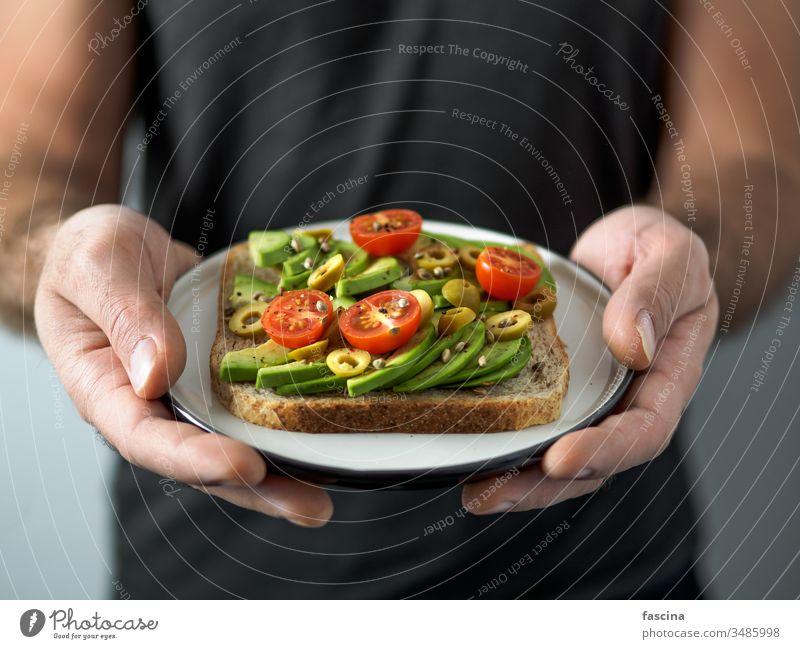 Veganes Sandwich mit Avocado in Männerhänden Belegtes Brot Veganer Hand Zuprosten Veggie Avocado-Toast Teller pflanzlich verzehrfertig Ideen Gesundheit