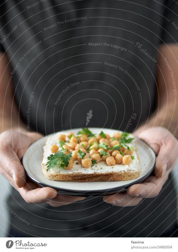 Veganes Sandwich mit Kichererbsen in Männerhänden Belegtes Brot Veganer Hand Zuprosten Teller verzehrfertig Textfreiraum Ideen Gesundheit Frühstück Mittagessen