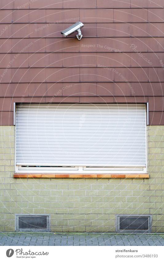 Mit Sicherheit - Fenster mit herabgelassenen Rolläden und einer Sicherheitskamera Haus Kamera verschlossen abweisend wohnen Wohngebiet Wand Fassade