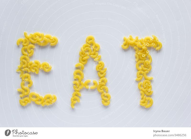 Wort essen von ungekochten gelben Nudeln auf dem weißen Grund. Spätzle Speisekarte Lebensmittel Küche Makkaroni Italienisch Essen roh Penne Gesundheit Textur