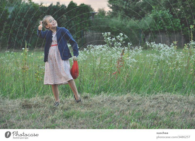 mädchen steht in einer blumenwiese in der natur und hält den daumen nach oben Kind Mädchen Wiese Natur Blumenwiese Feld Acker auf dem Land Landschaft Sommer