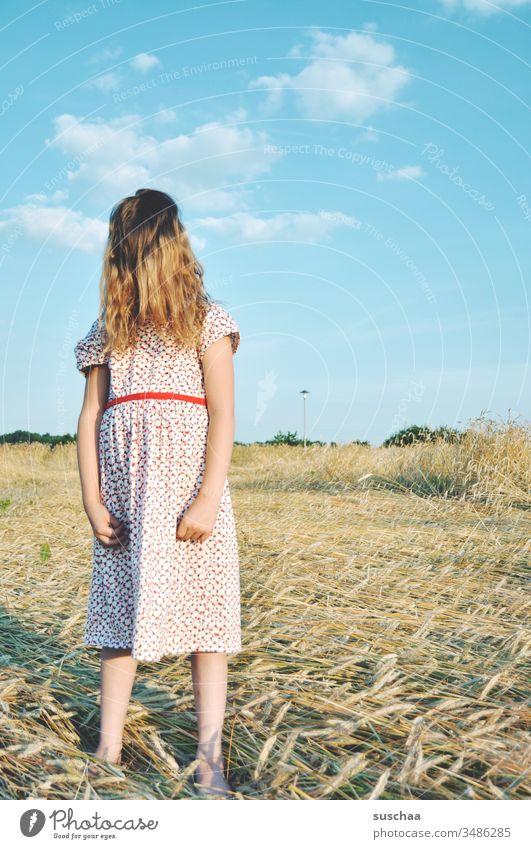 mädchen im sommerkleid auf einem strohacker mit haaren im gesicht Kind Mädchen Sommer Feld Acker Sommerkleid Kindheit Hand Finger Arme Himmel Strohacker