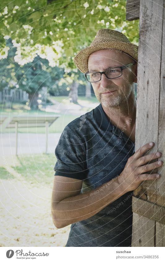 mann mit strohhut steht in einem sommerlichen park und schaut verträumt .. was mag er wohl denken? Mann Hut Strohhut Sommer Park Gelände Zoo Holzgestell