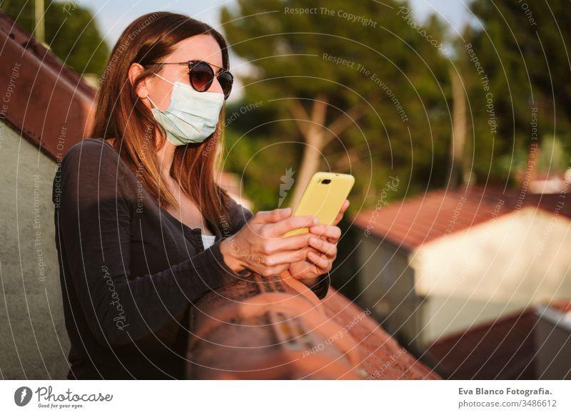 junge Frau zu Hause auf einer Terrasse, die eine Schutzmaske trägt, ein Mobiltelefon benutzt und einen sonnigen Tag genießt. Coronavirus Covid-19-Konzept Handy
