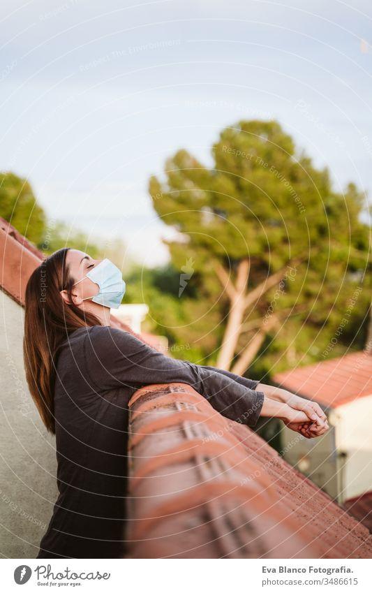 junge Frau zu Hause auf einer Terrasse, die eine Schutzmaske trägt und einen sonnigen Tag genießt. Coronavirus Covid-19-Konzept covid-19 schützend Mundschutz