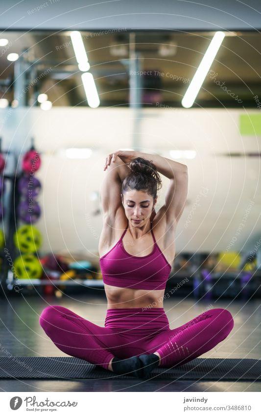 Junge Frau macht Dehnungsübungen auf einer Yogamatte strecken Unterlage Waffen Fitnessstudio Körper passen Bein Mädchen Sitzen Gesundheit Übung Lifestyle