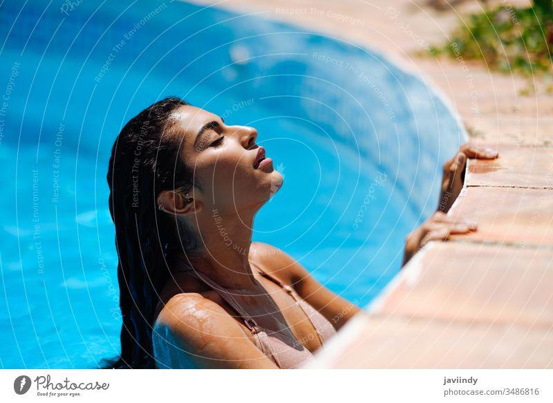 Schöne arabische Frau, die sich im Swimmingpool entspannt. Pool Schwimmsport Sommer schön Bikini jung Wasser Mädchen Sonnenbad Schönheit Körper attraktiv sonnig