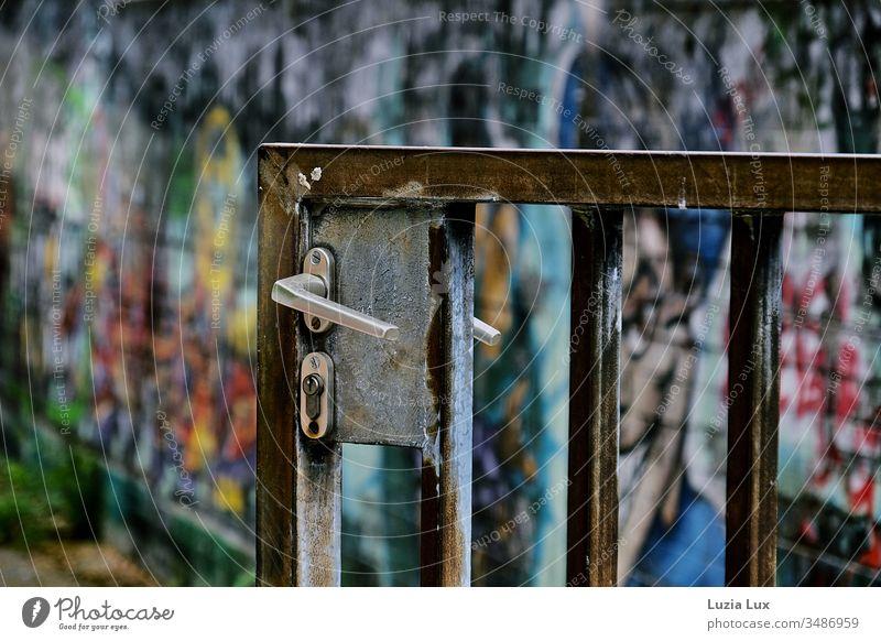 Eingangstor aus Metall mit Patina, dahinter bunte Graffitis Tor Türgriff Schloss Rost außen Hof Stadt urban Schule menschenleer sonnig Sonnenlicht