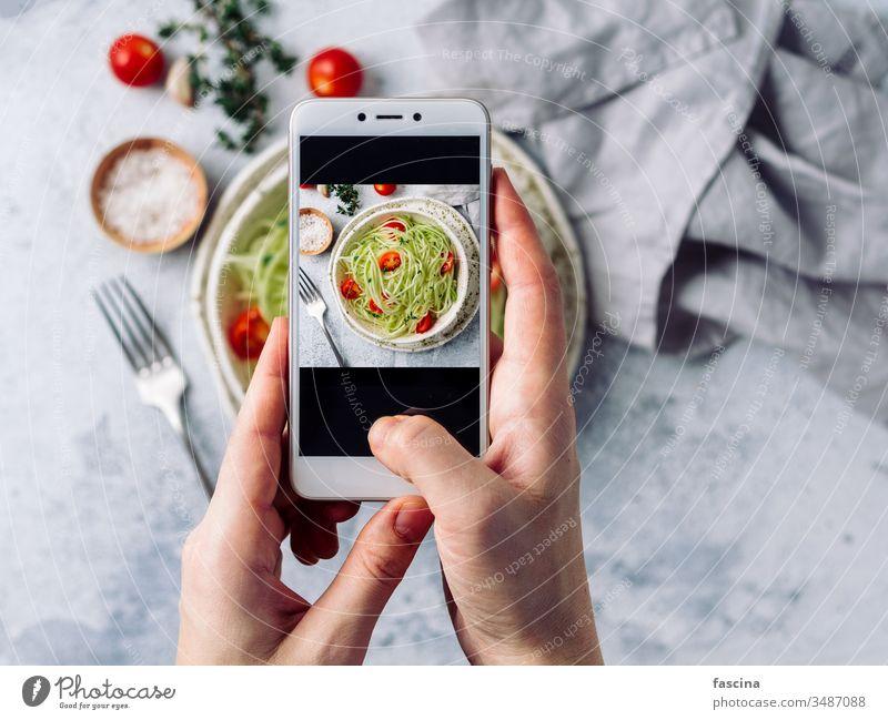 Zucchini-Nudelsalat. Draufsicht, Kopierraum Smartphone Fotografie Frau Hand Halt Telefon klug nehmen sozial roh Salatbeilage Nudeln zoodles Spaghetti Diät