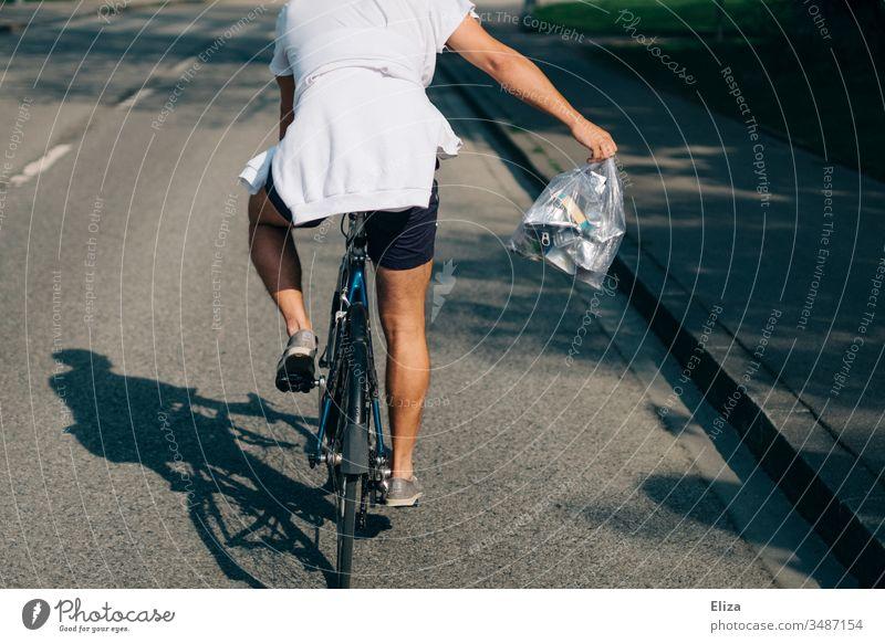 Ein Mann im Sommer auf einem Fahrrad mit einer Tüte voller Metallmüll beim Müll wegbringen; Recycling, Mülltrennung Fahrradfahrer Fahrradfahren Radfahrer Aktion