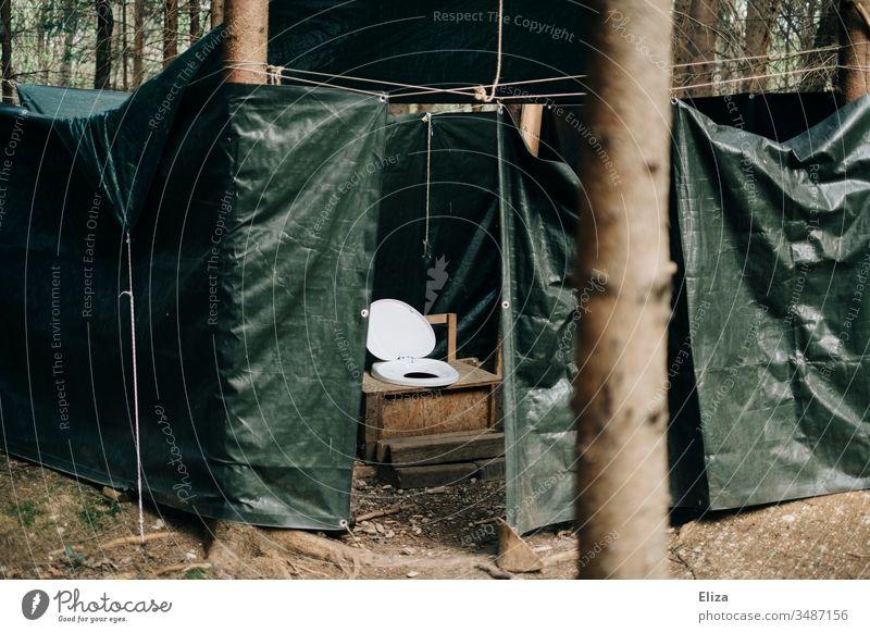 Eine Outdoor Toilette mit Planen geschützt draußen im Wald; Camping, Ferienlager, Plumpsklo, Klo outdoor zelten Menschenleer Farbfoto Außenaufnahme Natur