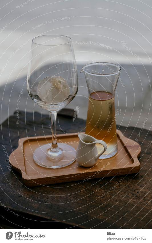 Ein Tablett mit einem Glas und einer Karaffe gefüllt mir einer hellen Flüssigkeit Weinglas Eistee Eiswürfel Sommer draußen servieren Gastronomie edel Alkohol