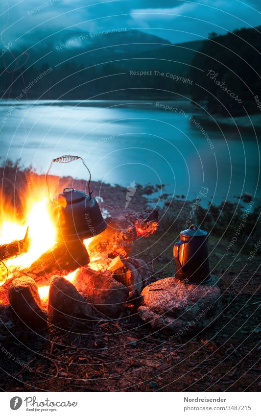 Lagerfeuer mit Kaffeekanne und Wasserkessel an einem Fluss in der Wildnis bei Nacht lagerfeuer kaffee kaffeekanne wasser fluss outdoor abend nacht blaue stunde