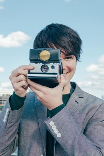 Junger gemischtrassiger Fotograf mit Polaroidkamera auf der Themse Lächeln altehrwürdig Business Tourist jung reisen Europa Ferien Sehenswürdigkeiten Himmel