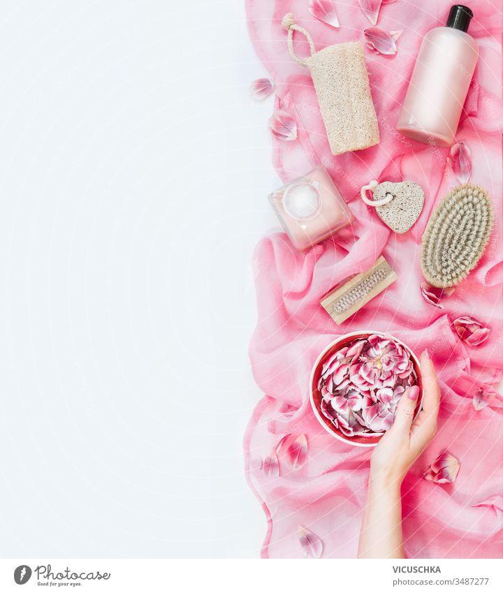 Frau hält eine Wasserschüssel mit Blumen auf rosa Handtuch mit verschiedenen umweltfreundlichen Hautpflege- und Schönheitsmitteln: Pinsel, Schwamm, Bimsstein und Kosmetikprodukte auf weißem Hintergrund. Ansicht von oben. Flach liegend